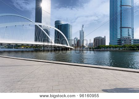 modern buildings and empty road in urban city at riverbank