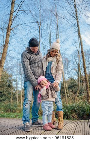 Happy couple with daughter enjoying together leisure in the forest