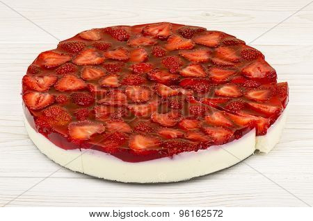 Strawberry cheesecake on the wooden background.