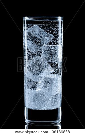 Glass with soda water and ice cubes.