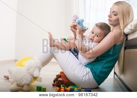 Cheerful young mom is embracing her little child