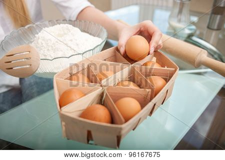 Young healthy housewife is preparing food in the kitchen