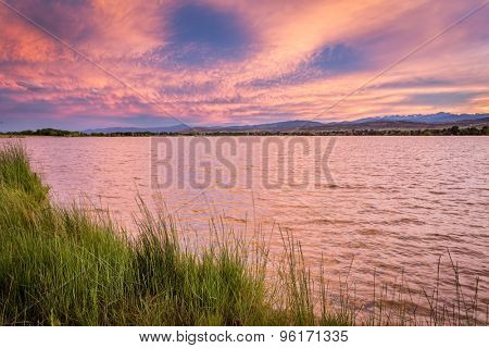 pink sunset cloudscape over a lake at foothills of Rocky Mountains in Colorado