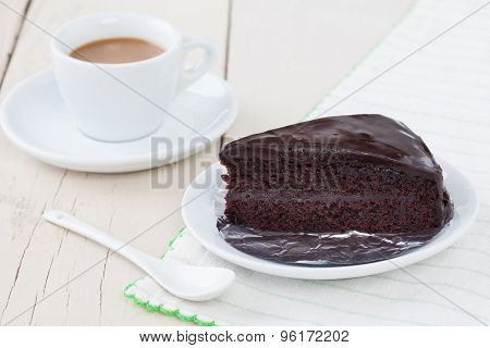 Dark Chocolate Cake On White Plate On Wooden Table With Coffee