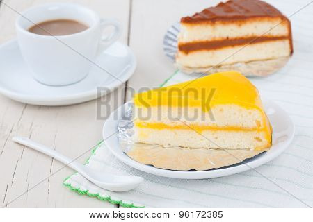 Orange Cake On White Plate On Wooden Table With Coffee And Coffee Cake
