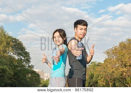 Young Asian Man And Woman Drinking Water From A Bottle And Thumbs-up