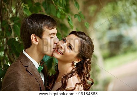 Close Up Of A Young Couple Visiting An Park With Man Kissing The Girl On Cheek During A Sunny Day.