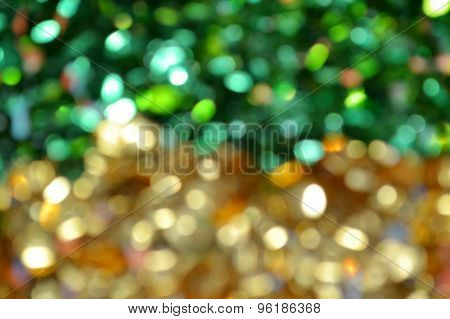 Bright and abstract blurred green and golden background with shimmering glitter