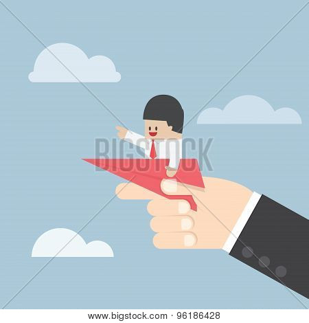 Businessman Sitting On Paper Plane With Big Hand Ready To Throw