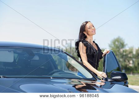 Beautiful young woman is opening the door of her transport