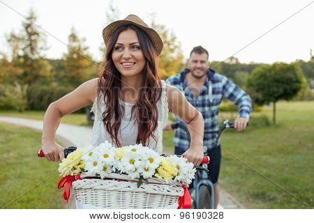 Pretty young girlfriend and boyfriend are driving bicycles
