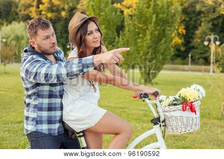 Nice young loving couple is cycling in park