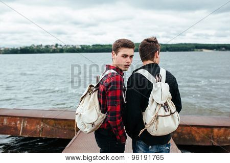 two young guys stand on the pier