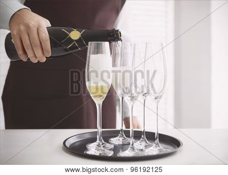 Professional Male Waiter In Uniform Pouring Champagne Into A Flute
