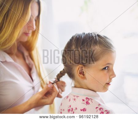 Mother Hairdressing Her Preteen Daughter At Home