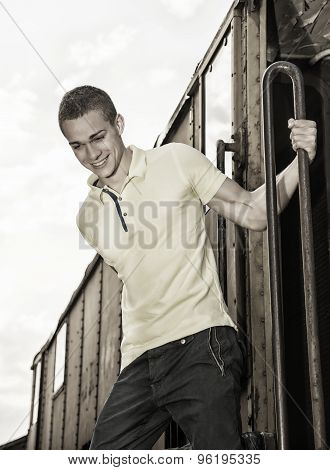 Fit guy with polo shirt hanging from old train, jumping