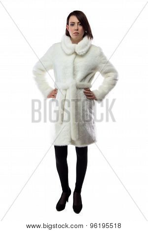 Woman in white fur coat with hands on hips