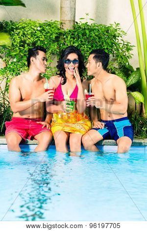 Asian friends drinking fancy cocktails at hotel or club pool