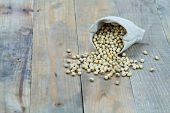 stock photo of soybeans  - Soybean in sack on vintage wooden boards still life - JPG