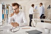 picture of sms  - Serious businessman writing or reading sms in working environment - JPG