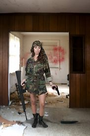 stock photo of m16  - Beautiful young woman soldier with a M16 rifle and a pistol - JPG