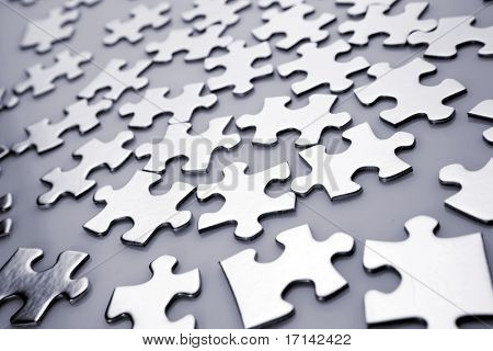 Scattered shiny jigsaw puzzle pieces