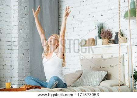 poster of Good morning. Pretty relaxed young woman stretching herself while sitting in bedroom and preparing to have breakfast.