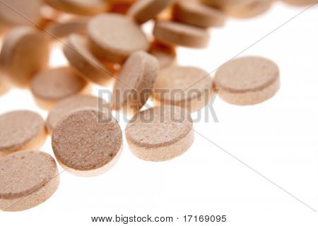 Vitamin tablets on plain background