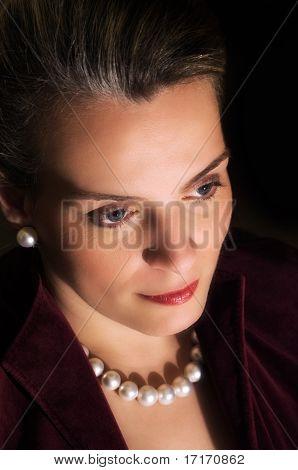 Junge schöne Frau In Abend Kleidung und Perlen