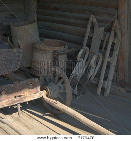 Ancient rural coach-house interior with wooden cart