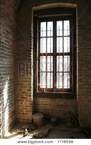 Old Window With Bars And Brick Wall