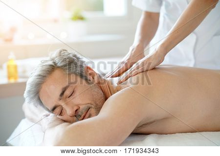 poster of Man relaxing on massage table receiving massage