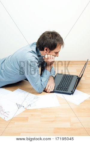 Young Man Using Laptop  Lying On The Floor In The Room
