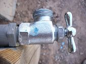 pic of bib tap  - Shiny hose bib (water faucet) in an up-discharge orientation. Body has bright but textured finish; handle is smooth shiny chrome.