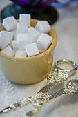 stock photo of sugar cube  - Sugar cubes piled in a small container with tongs in foreground - JPG