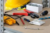 Electricians Tools And Supplies On Cork-covered Shelving poster
