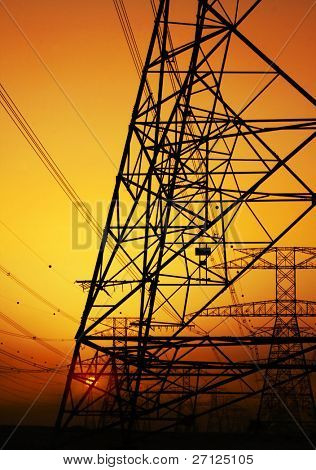 Electricity Pylon over orange sunset sky. Environmental damage