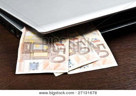 Closeup to laptop and euro banknotes