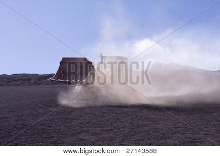 bulldozer during work covered in dust clouds