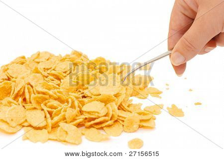 Female hand with a spoon of corn flakes