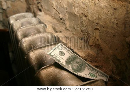 One hundred dollars bank note on an old radiator