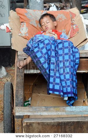 JAKARTA, INDONESIA - SEPTEMBER 20: A young street child sleeps in a trash cart on Hari Raya, the end of a month of fasting called Ramadan Jakarta September 20, 2009 in Jakarta.
