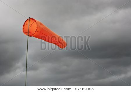 Full windsock under a stormy sky