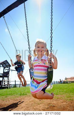 Kind auf Schaukel im Spielplatz im freien