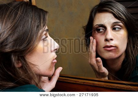 Battered woman checks the extent of her injuries in the bathroom mirror