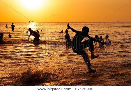 Young boy jumps in the ocean and makes a splash at sunset