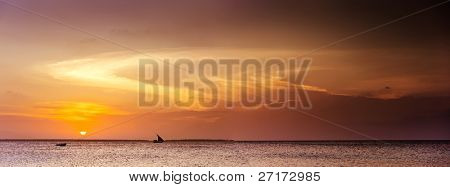 amazing panoramic seascape with a sail boat on horizon and sunset lighting up cloudscape