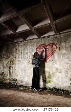 Graffiti artist paints a love valentine heart on grunge wall