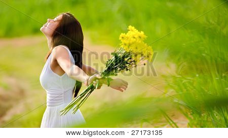 Carefree adorable girl with arms out in field. summer freedom andjoy concept.