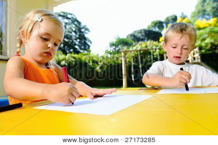 cute adorable young kids with crayons at an outside playschool